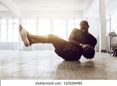 Athletic man doing abdomen exercise on the floor. Man doing workout using a medicine ball at the gym.