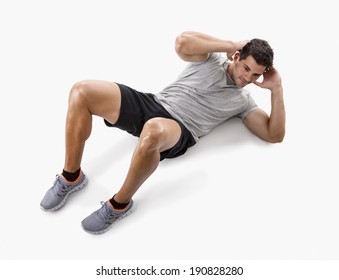 Athletic man doing abdominals, isolated over a white background