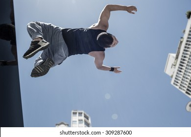 Athletic man doing back flip in the city on a sunny day