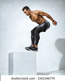 Athletic man doing a box jump exercise routine. Photo of muscular man on grey background. Strength and motivation. Full length. Side view