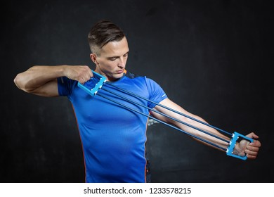 Athletic man doing exercises for hands in a studio.