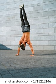 Athletic man doing handstand. Photo of young man training in the city. Full length