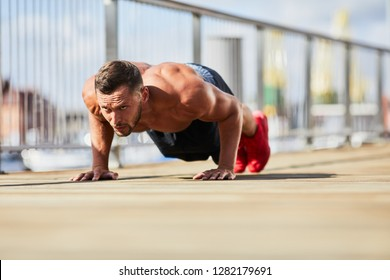 Athletic man doing pushup exercise outdoors