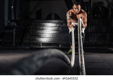 Athletic man doing some training exercises with a rope in gym. Attractive muscular man working out with heavy ropes.