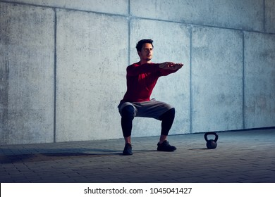 Athletic man doing squat exercise