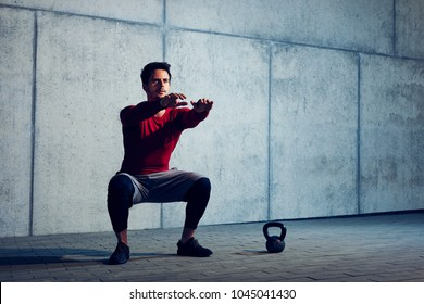 Athletic man doing squats preparing to do kettlebell exercises