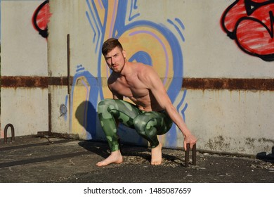 Athletic man doing stretching exercise outdoor