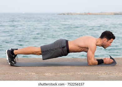 Athletic man during forearm plank exercise outside on the waterfront