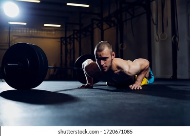 Athletic man exercise at gym doing burpee over the bar