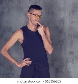 Athletic man with glasses thinking what to do before a workout. Where to train?