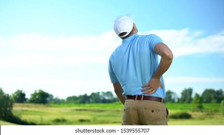 Athletic man golfer suffering sharp lower back pain, sport trauma, health