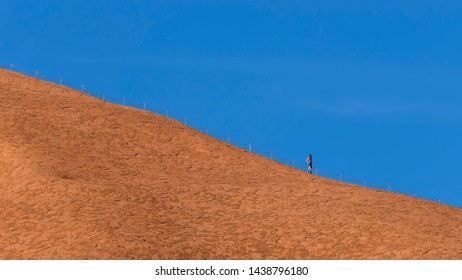 Athletic man with his face covered by a net to protect himself from insects on top of Uluru, Ayers Rock, Australia
