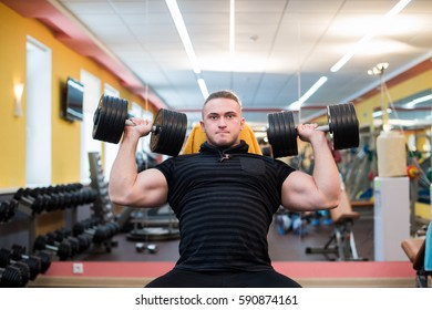 Athletic man is holding the barbell over the head at the gym
