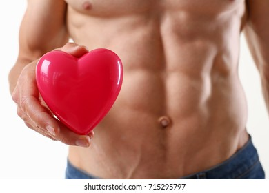 Athletic man holds a heart in his hand
