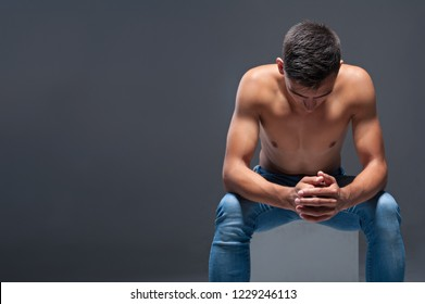 Athletic man in jeans sits