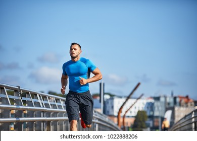 Athletic man jogging, running  in the city