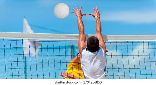 Athletic man jumping to make wall block at beach volleyball net.