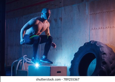 Athletic man jumping on fit box in gym. Crossfit training workout. Male with naked torso exercises jump on the dark background. Functional training.