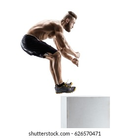 Athletic man jumping onto a box as part of an exercise routine. Side view of handsome man in sportswear isolated on white background.