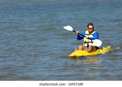 Athletic man kayaking on lake