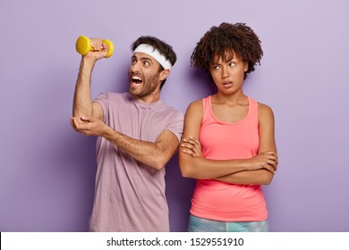 Athletic man lifts dumbbell, has weary workout, wears headband and t shirt, unhappy bored woman stands with arms folded, motivates husband for sport, stand shoulder to shoulder. Bodybuilding.