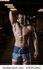 Athletic man with a muscular body poses in the gym, showing off his muscles. The concept of a healthy lifestyle