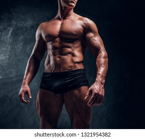 Athletic man with muscular body wearing underwear. Cropped photo in a studio with dark wall background