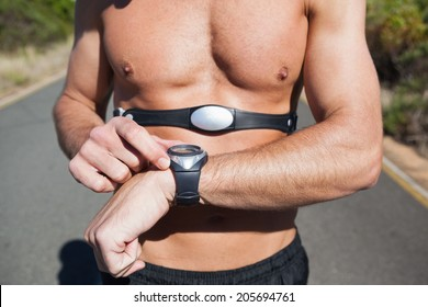 Athletic man on open road with monitor around chest on a sunny day