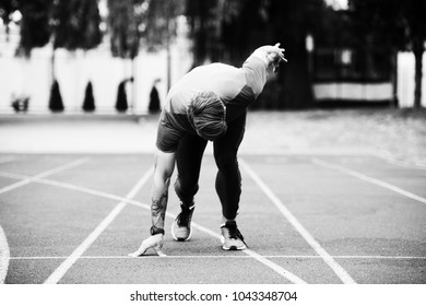 Athletic Man on Running Track Getting Ready to Start Run