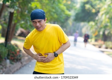 Athletic man on running track has side cramps during workout