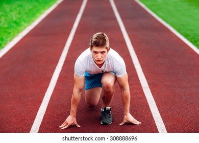 Athletic man on track starting to run. Healthy fitness concept with active lifestyle.