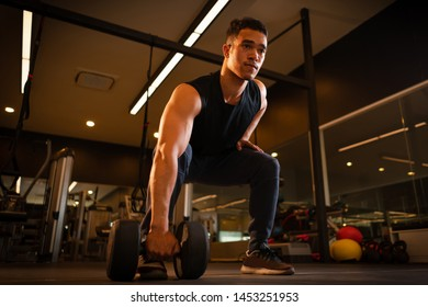 Athletic man playing dumbbell exercise for arm endurance training exercise to strengthen and tone the shoulder muscles. concept of weight training.