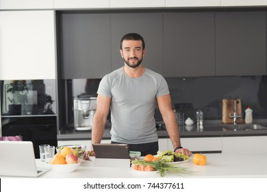 Athletic man posing in the kitchen. Before him on the table are various vegetables and fruits. It is located in a modern kitchen.