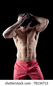 athletic man posing nude in dark with hat