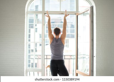 Athletic man practicing yoga in white well-lit studio with big window. Vrikshasana, tree pose