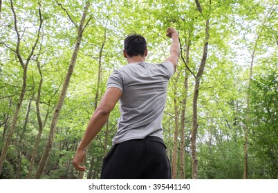 athletic man raising one arms in the forest. winner and success concept