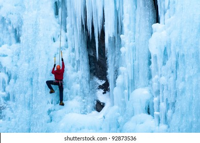 Athletic man in red coat with orange helmet and gold ice tools climbing a large blue wall of ice at the Ouray Ice Park