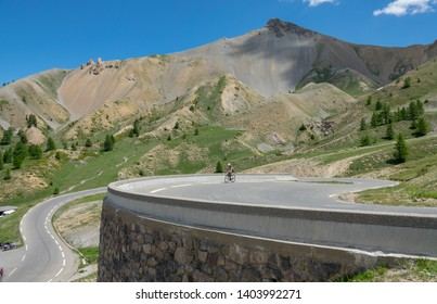 Athletic man riding a road bike along the scenic switchback road in the sunny French Alps. Active male tourist enjoying a bicycle road trip across the Alps via the famous Route des Grandes Alpes.
