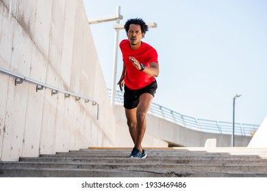 Athletic man running and doing exercise outdoors.
