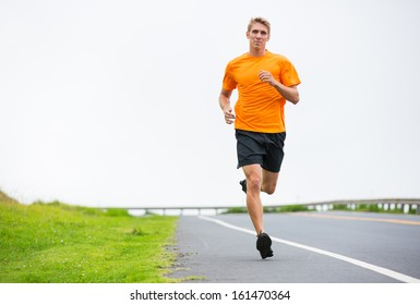 Athletic man running outside, training outdoors. Jogging on road