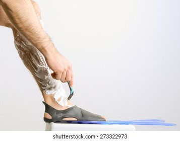 Athletic man shaving leg.