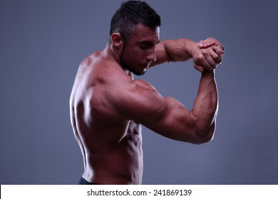Athletic man showing his muscles over gray background