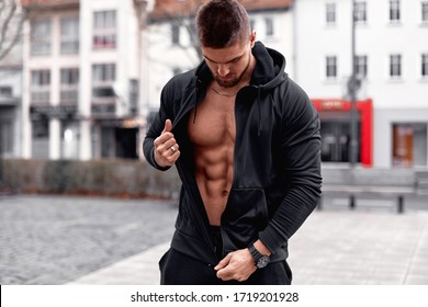 Athletic man shows the ABS in a black tracksuit on a city background