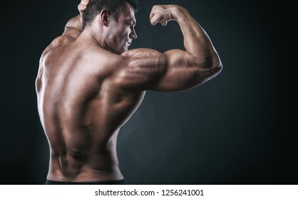 Athletic man shows his muscular back and hands on a dark background. Sport concept