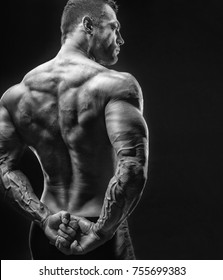 Athletic man shows his muscular back on a dark background. Black and white image