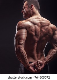 Athletic man shows his muscular back on a dark background