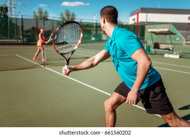 Athletic man and slim woman on tennis training