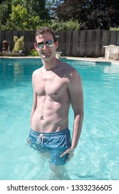 Athletic man standing in an outdoor swimming pool looking at camera with defined abs. Healthy and active man posing in a pool water up to his waist on a summer day.