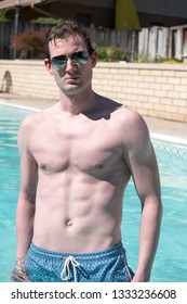 Athletic man standing in an outdoor swimming pool with defined abs. Healthy and active man posing in a pool water up to his waist on a summer day. Confident man in a backyard pool looking at camera.