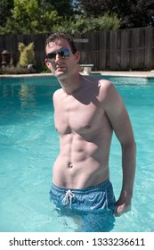 Athletic man standing in an outdoor swimming pool looking at camera with ripped abs. Healthy and active man posing in a pool water up to his waist on a summer day.